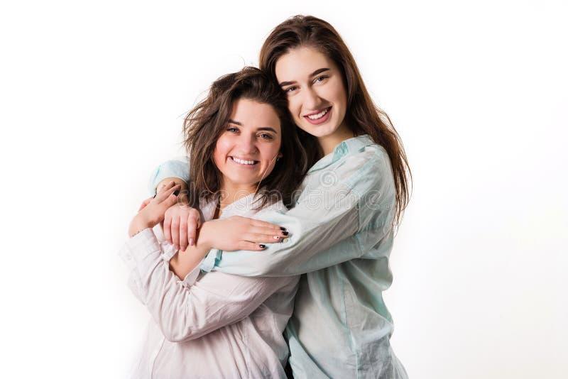 Deux jeunes filles étreignent sur un fond blanc photographie stock