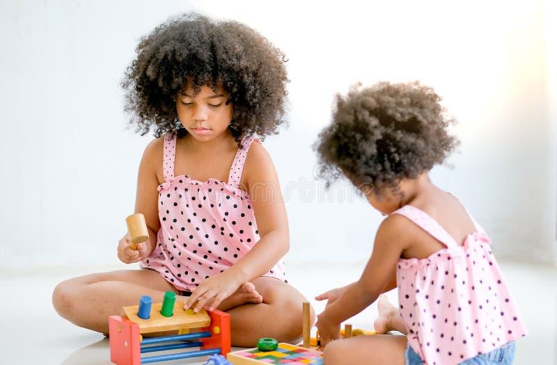 Deux jeunes filles africaines jouent les jouets ainsi que le foyer principal sur la fille latérale gauche qui regardent pour se c image stock