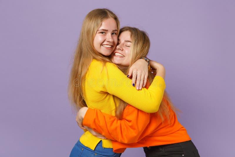 Deux jeunes filles blondes assez joyeuses de soeurs de jumeaux dans des vêtements colorés vifs étreignant regardant la caméra d'i photos libres de droits