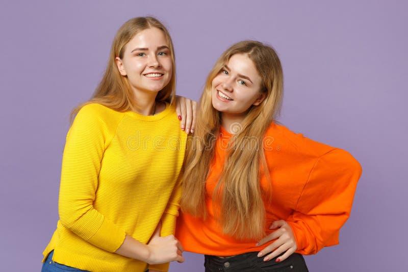 Deux jeunes filles blondes de sourire de soeurs de jumeaux dans la position colorée vive de vêtements, regardant la caméra d'isol photos libres de droits