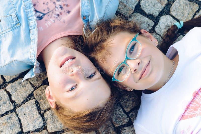 Deux jeunes filles blondes se trouvant au sol avec des yeux ouverts et leurs têtes côte à côte photo stock
