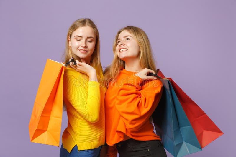 Deux jeunes filles blondes songeuses de soeurs de jumeaux dans des vêtements vifs tenant le sac de paquet avec des achats après l photo stock