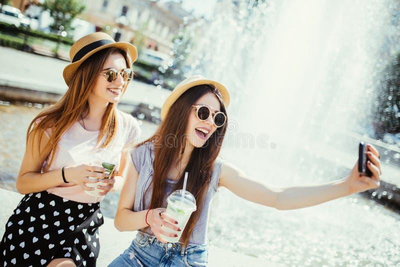 Deux jeunes filles dans les lunettes de soleil et des chapeaux près de fontaine de ville Les meilleurs amis boivent des cocktails photographie stock