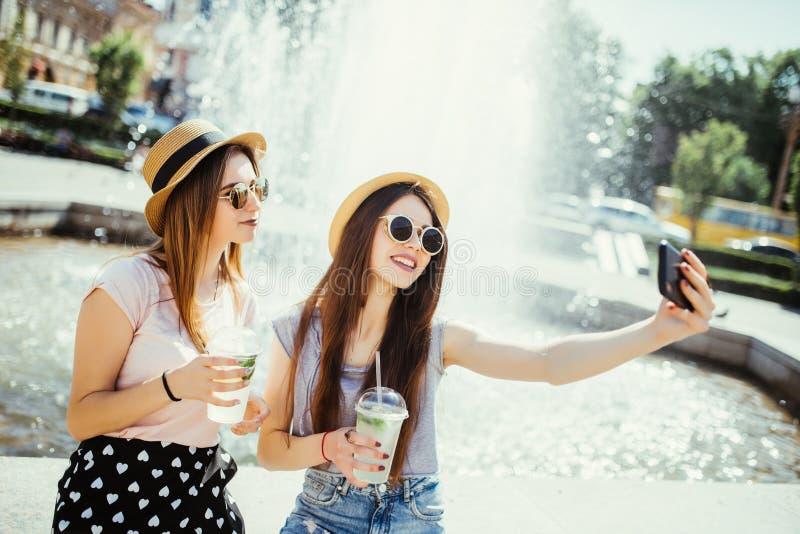 Deux jeunes filles dans les lunettes de soleil et des chapeaux près de fontaine de ville Les meilleurs amis boivent des cocktails image stock