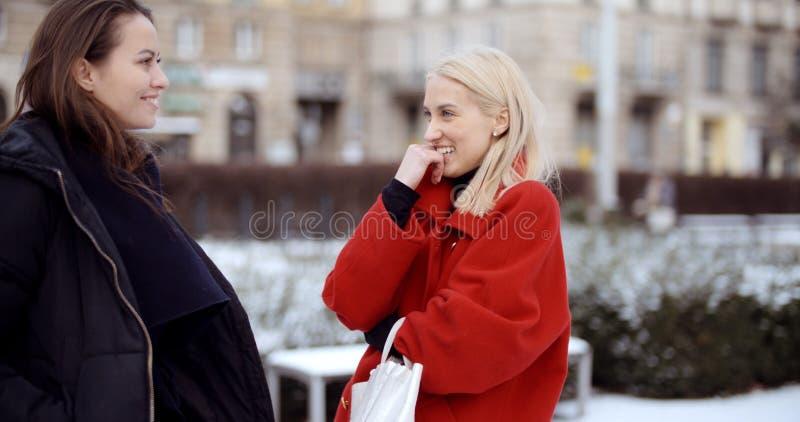 Deux jeunes filles dans une ville appr?ciant le temps photo stock
