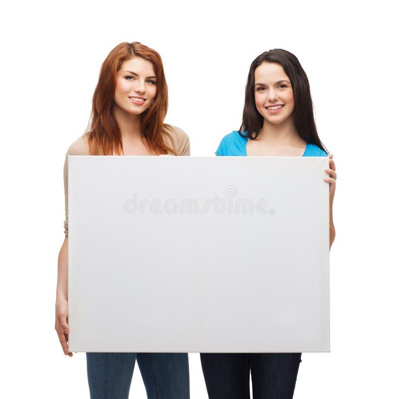 Deux jeunes filles de sourire avec le conseil blanc vide image libre de droits