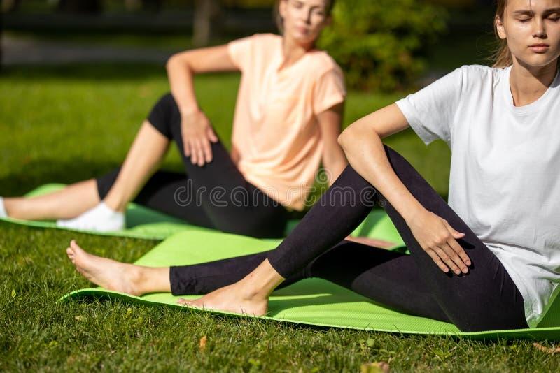 Deux jeunes filles faisant l'étirage sur des tapis de yoga sur l'herbe verte en parc sur l'air ouvert image libre de droits