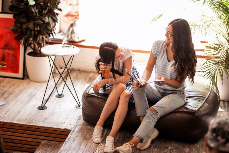Deux jeunes filles minces avec de longs cheveux foncés, équipement occasionnel de port, regard à un livre dans un café moderne image stock