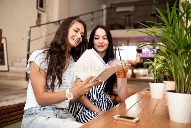 Deux jeunes filles minces avec de longs cheveux foncés, équipement occasionnel de port, regard à un livre dans un café moderne images stock