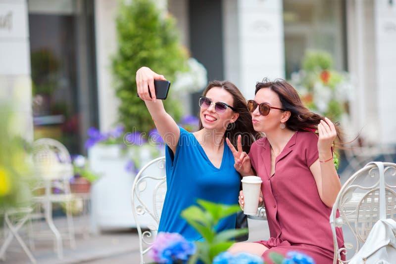 Deux jeunes filles prenant le selfie avec le téléphone intelligent au café d'extérieur Deux femmes après l'achat avec des sacs se photo stock
