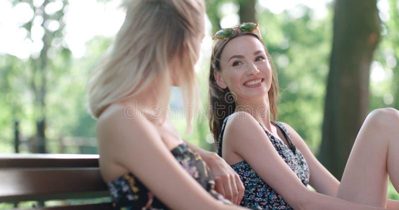 Deux jeunes filles s'asseyant sur le banc en parc appréciant l'été et la causerie image stock