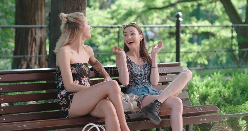 Deux jeunes filles s'asseyant sur le banc en parc appréciant l'été et la causerie photos libres de droits