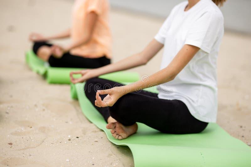 Deux jeunes filles s'asseyent en positions de lotus sur des tapis de yoga sur la plage sablonneuse un jour chaud photos libres de droits