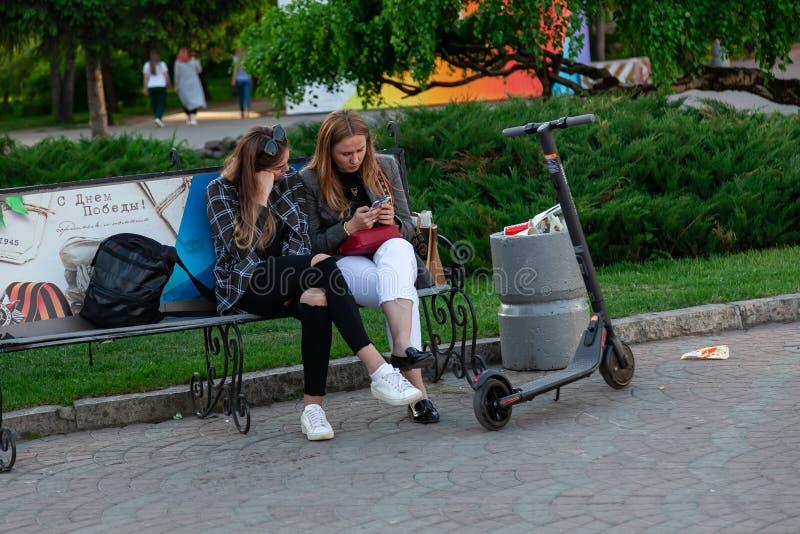 Deux jeunes filles s'asseyent sur un banc et regardent un smartphone en parc de ville avec les plantes vertes près d'un scooter é image libre de droits