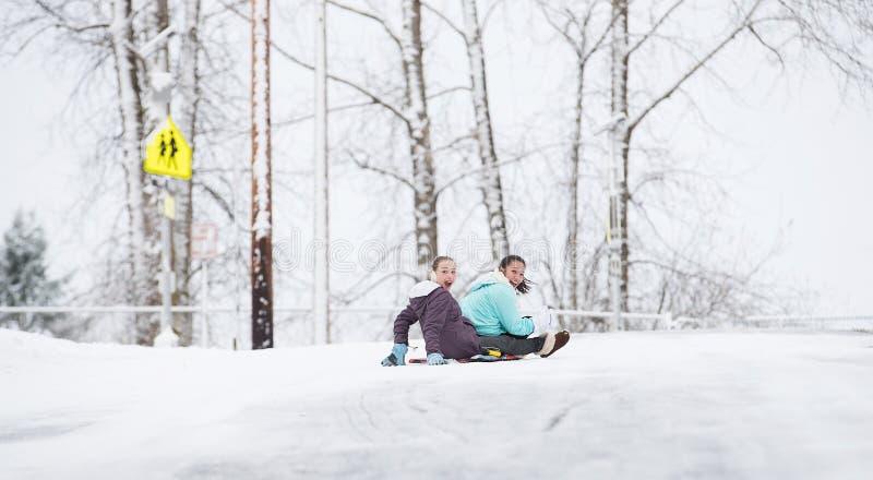 Deux jeunes filles sledding en bas de la colline dans la glace et la neige photographie stock