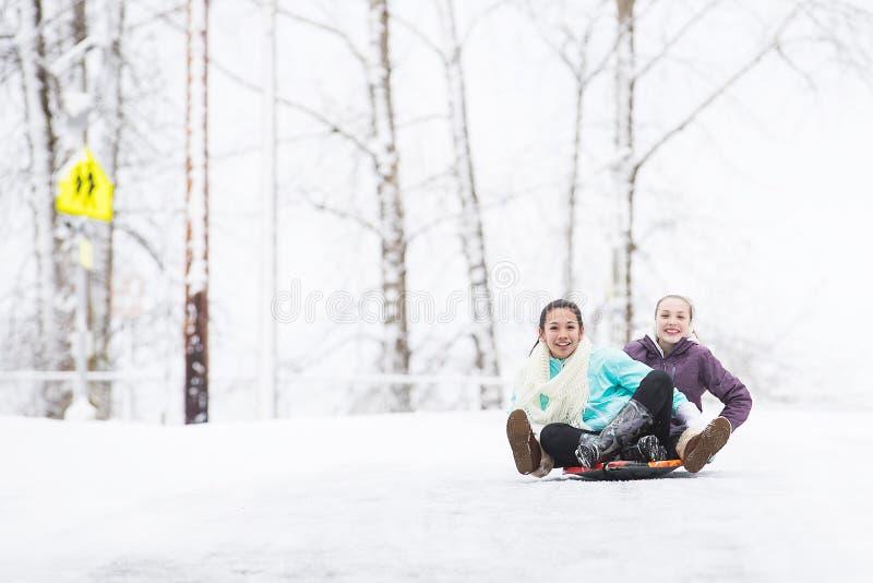 Deux jeunes filles sledding en bas de la colline dans la glace et la neige images libres de droits