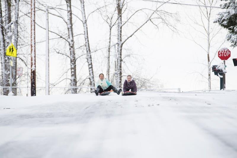 Deux jeunes filles sledding en bas de la colline dans la glace et la neige photos libres de droits
