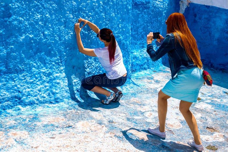 Deux jeunes filles sont photographiées contre le mur bleu à Rabat, Maroc La ville pittoresque bleue et blanche célèbre photos stock