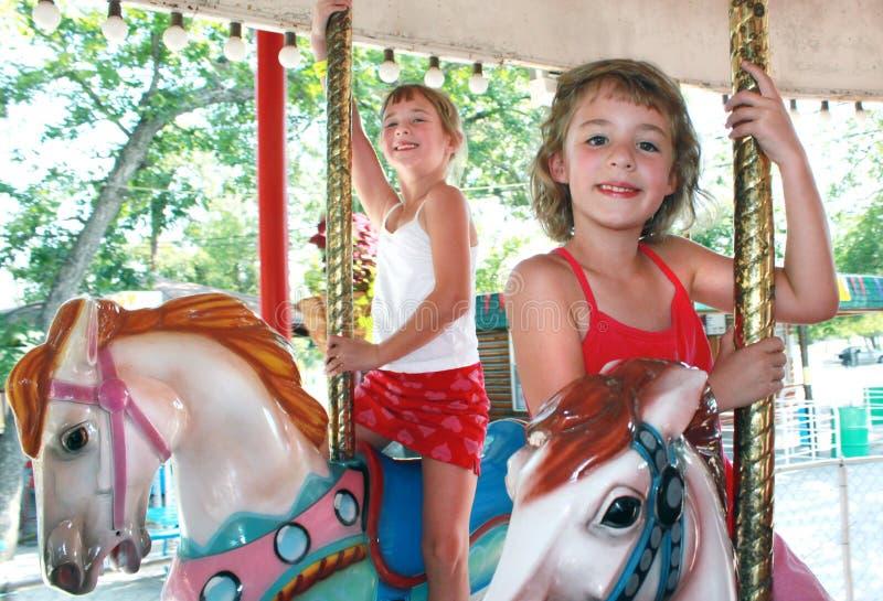 Deux jeunes filles sur le carrousel photographie stock
