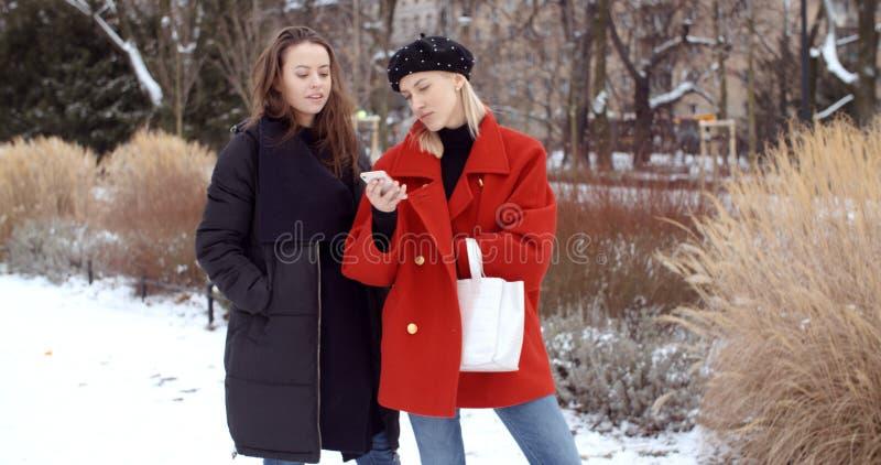 Deux jeunes filles utilisant le t?l?phone portable dans une ville photos stock