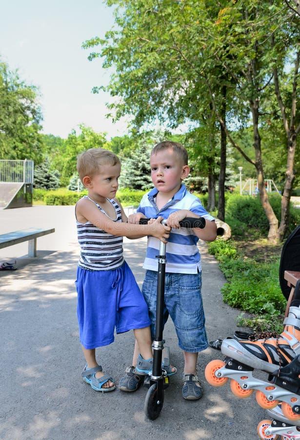 Deux jeunes garçons avec un scooter photographie stock libre de droits