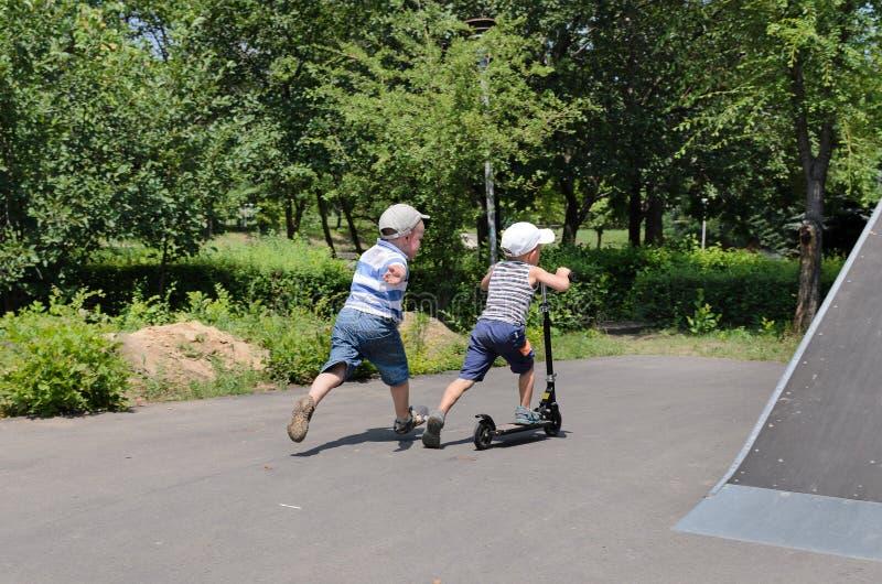 Deux jeunes garçons jouant avec un scooter photos stock