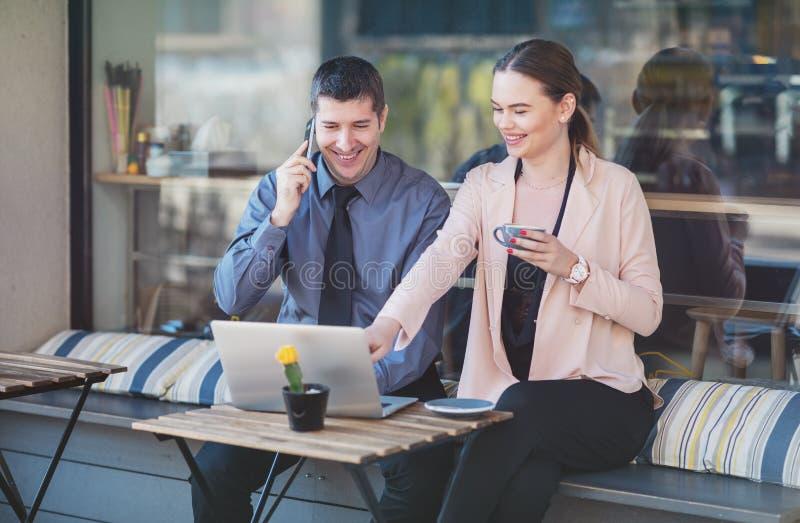 Deux jeunes gens d'affaires élégants qui tiennent une réunion informelle pour prendre un café - Un couple heureux assis sur une t images libres de droits
