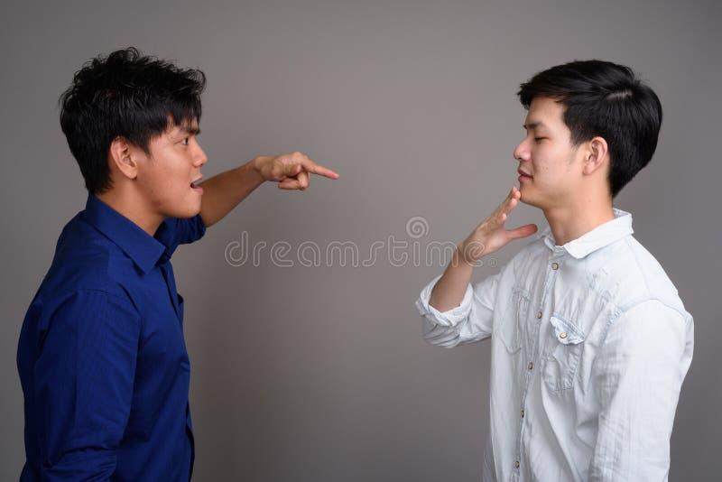 Deux jeunes hommes asiatiques beaux ayant l'argument photo libre de droits
