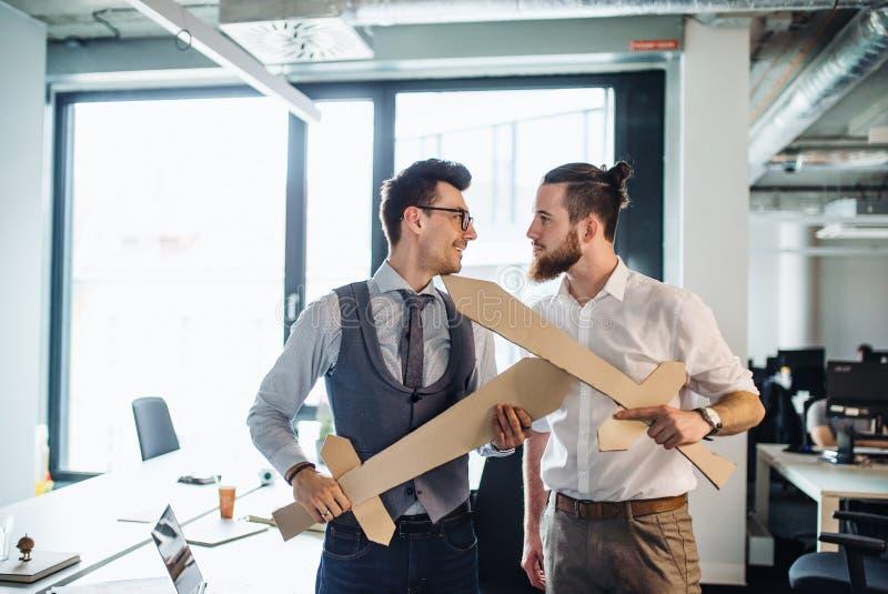 Deux jeunes hommes d'affaires avec des ?p?es dans un bureau, ayant l'amusement Un concept de concurrence photo stock