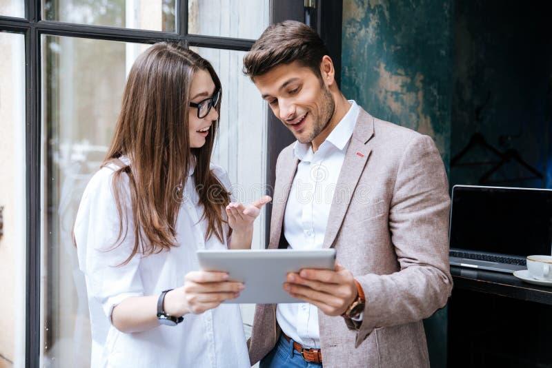 Deux jeunes hommes d'affaires travaillant sur l'ordinateur portable dans le café photo libre de droits