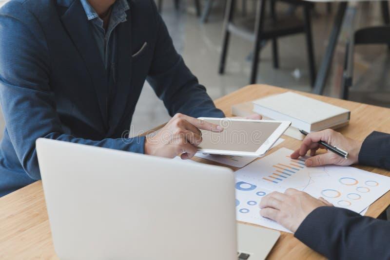 deux jeunes hommes d'affaires utilisant le touchpad et le graphique de gestion d'analyse images stock
