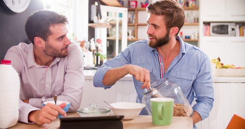 Deux jeunes hommes mangeant le petit déjeuner dans la cuisine ensemble photo stock