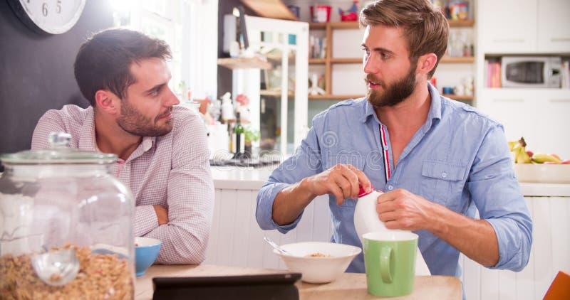 Deux jeunes hommes mangeant le petit déjeuner dans la cuisine ensemble photographie stock libre de droits