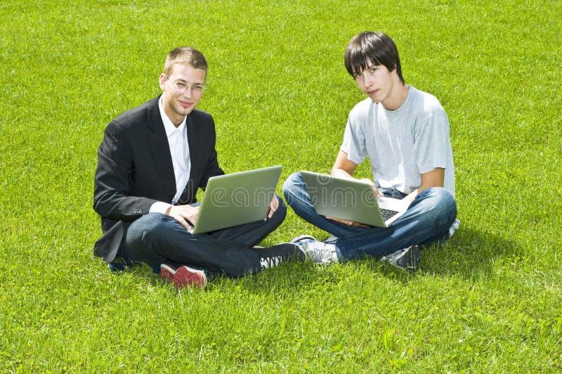 Deux jeunes hommes s'asseyant sur l'herbe avec leurs ordinateurs portatifs image libre de droits