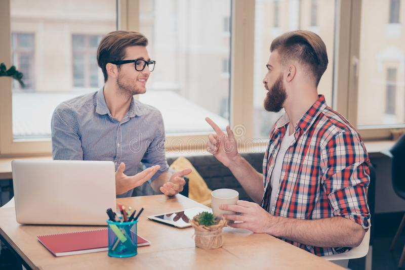 Deux jeunes indépendants travaillant en ligne sur le projet prévoit des meilleurs amis parlant ayant la conversation en café rega photographie stock libre de droits