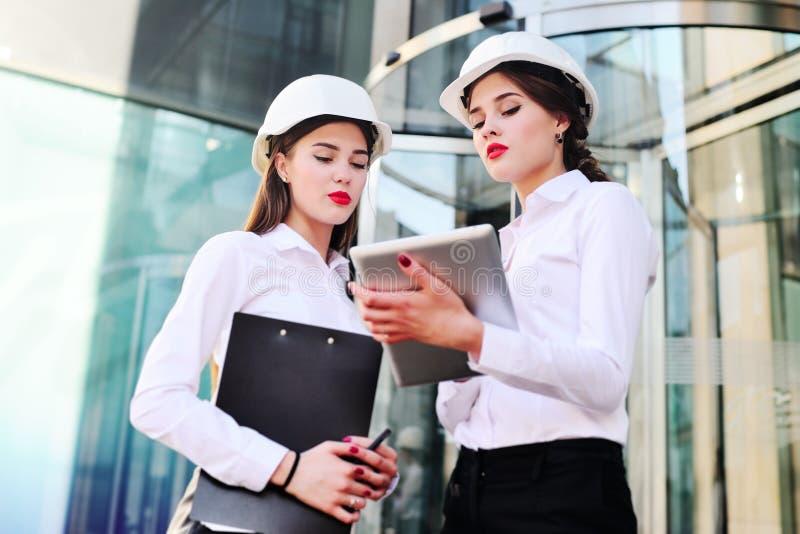 Deux jeunes jolis ingénieurs industriels de femmes d'affaires dans des casques de construction avec un comprimé dans des mains su photos libres de droits