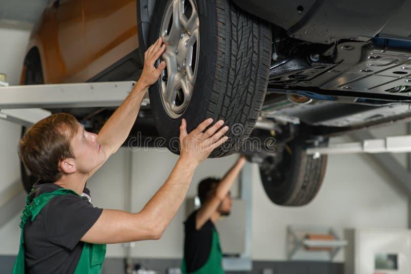 Deux jeunes mécaniques diagnostiquent la condition du suspensi du ` s de voiture photos libres de droits