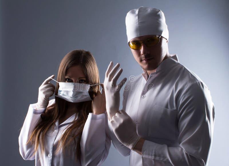 Deux jeunes médecins se préparant à l'opération dans la lumière contrastante photographie stock libre de droits
