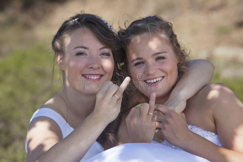 Deux jeunes mariées sourient et montrent leurs anneaux de mariage dans la bordure de nature photo libre de droits