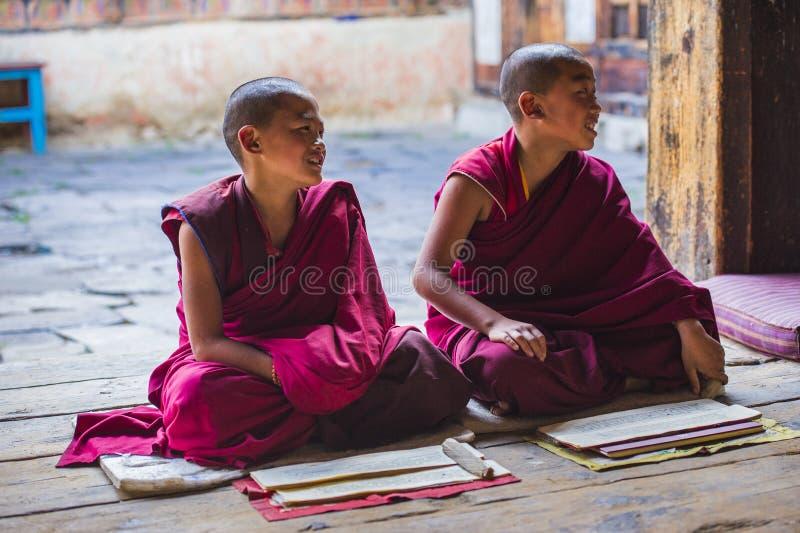 Deux jeunes moines de novice bouddhiste rit, quand ils s'asseyant sur le plancher, le Bhutan images stock