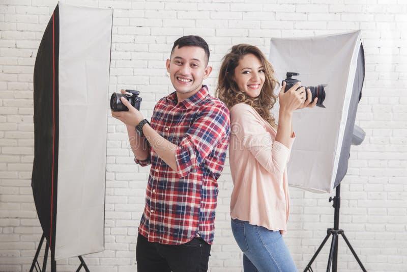 Deux jeunes photographes de nouveau au sourire arrière tout en regardant le Ca photo stock