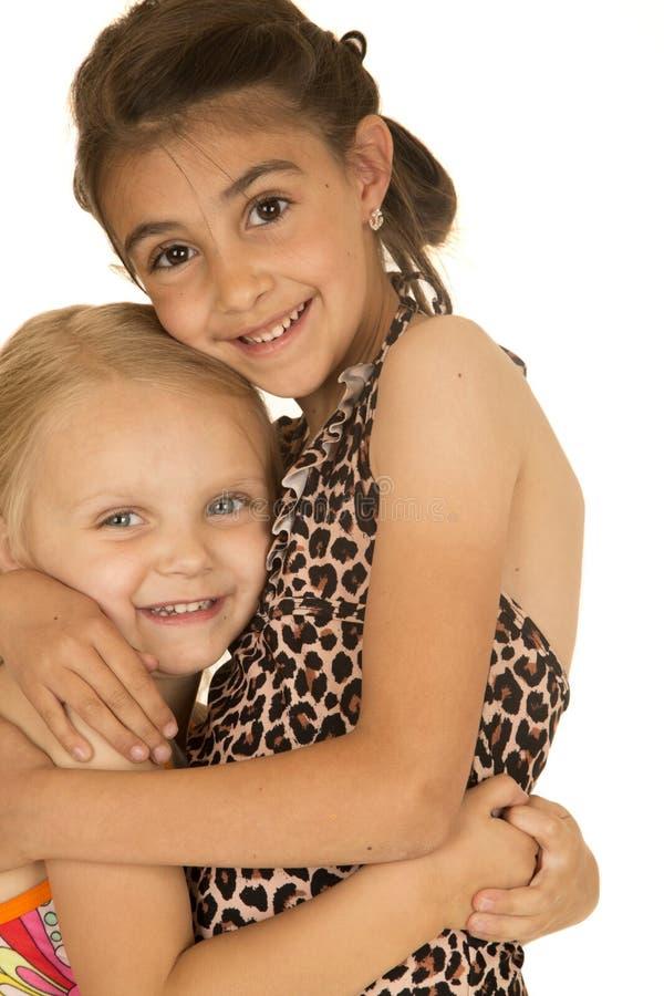 Deux jeunes soeurs mignonnes s'étreignant maillots de bain de port photographie stock libre de droits