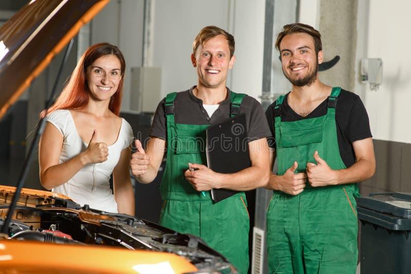 Deux jeunes travailleurs de service de voiture, et une belle exposition o de jeune fille image libre de droits
