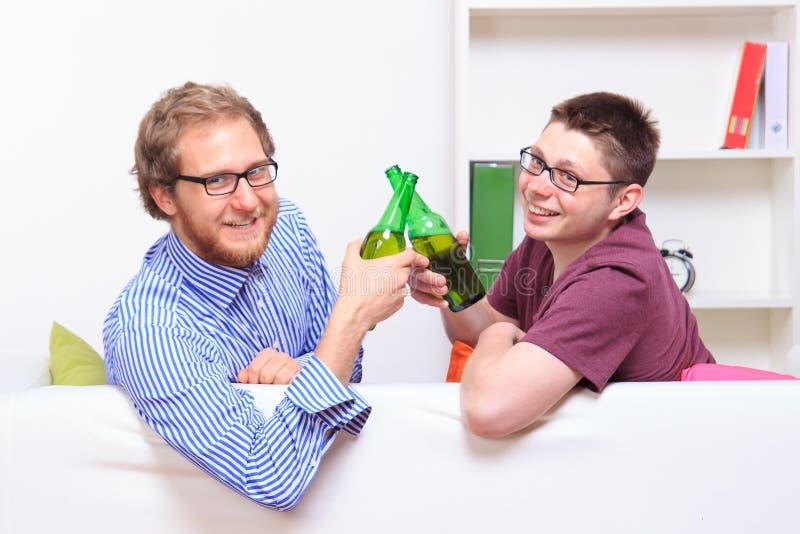 Deux jeunes types avec de la bière sur le sofa image libre de droits