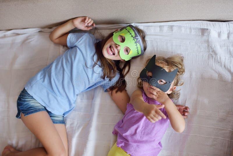 Deux jeux de filles l'imbécile dans un monstre de masque pour le chat noir de Halloween photos libres de droits