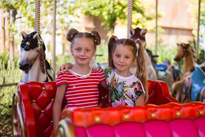 Deux jolies amies montent sur le carrousel photos libres de droits