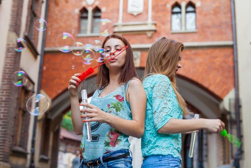 Deux jolies filles ayant l'amusement et soufflant des bulles Backgroun urbain photo stock