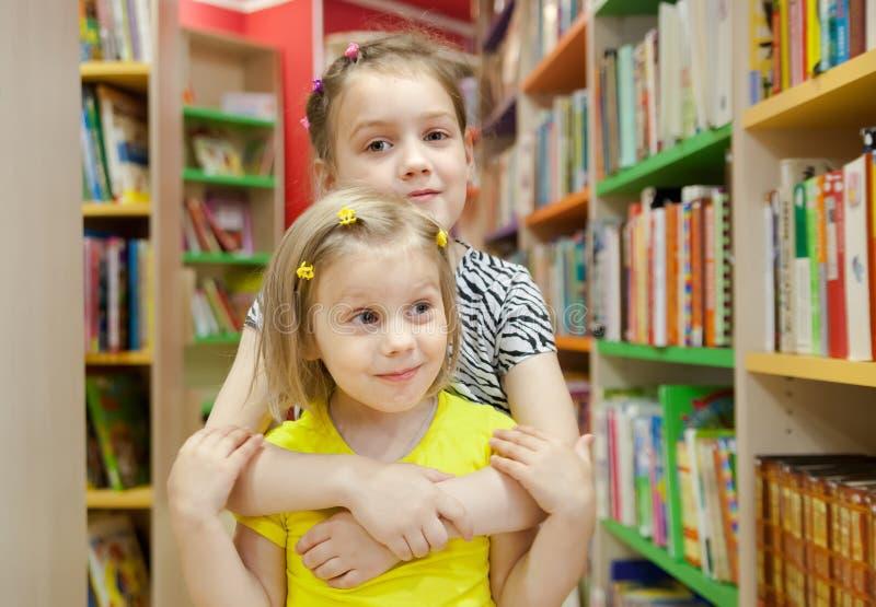 Deux jolies filles dans la bibliothèque images libres de droits