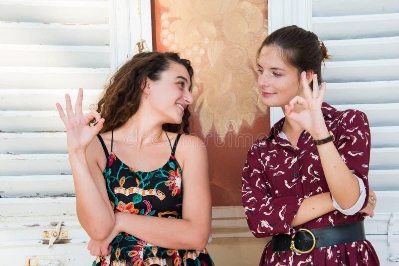 Deux jolies filles font le signe correct image stock