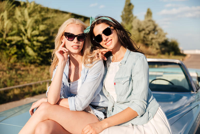Deux jolies jeunes femmes heureuses s'asseyant sur la voiture en été photos stock